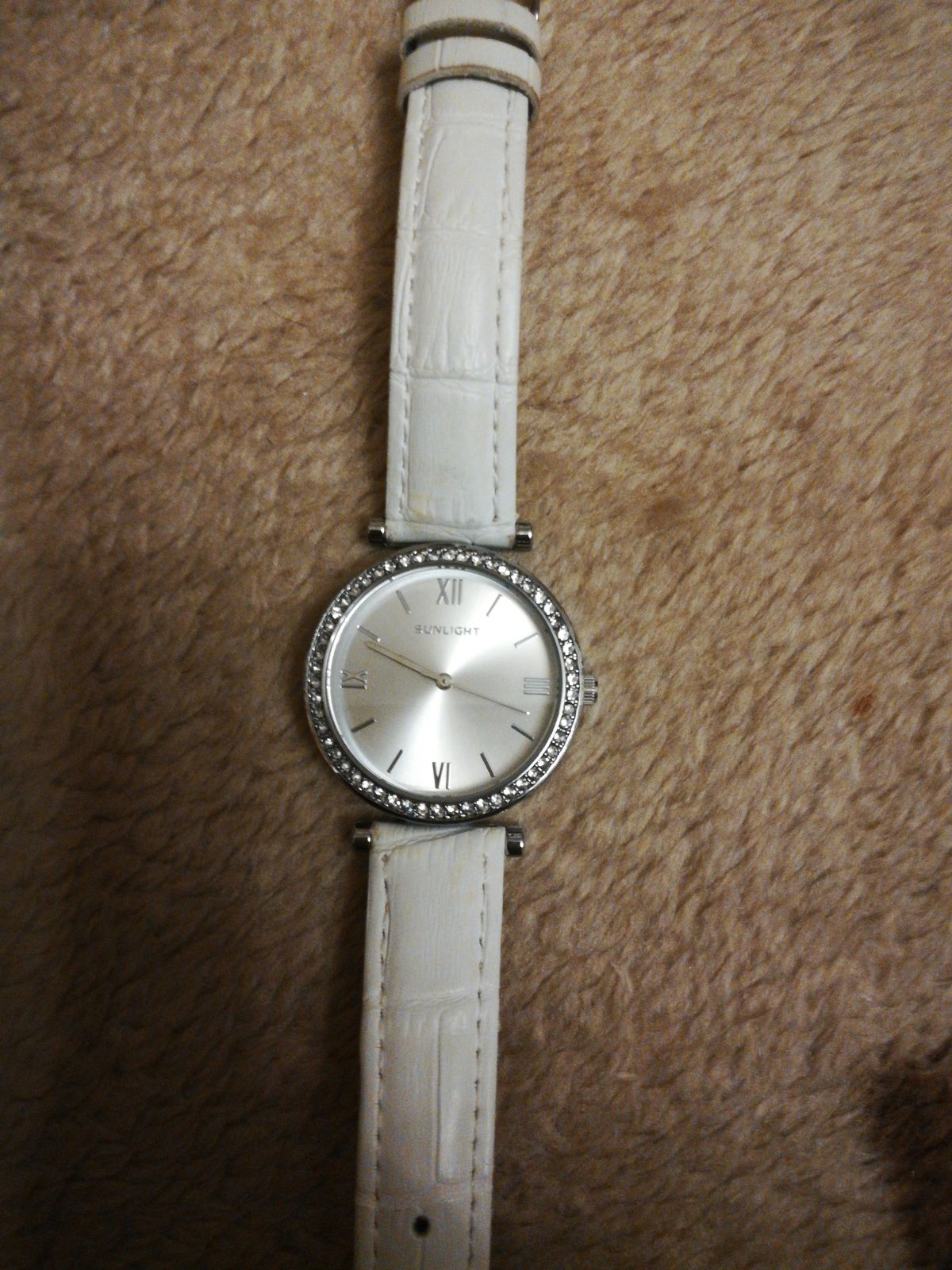 Часы наручные с белым ремешком.
